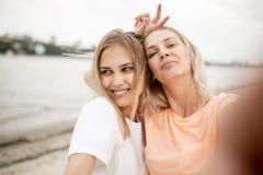两个年轻可爱的白肤金发的女孩在一个温暖的大风天采取在海滩的一selfie 免版税图库摄影