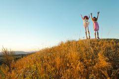 两个快乐的孩子在夏日以后跳并且举了-日落的手 免版税库存照片
