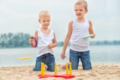 两个兄弟是走和使用在海滩 比赛是圆环抛 免版税库存照片