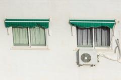 两个窗口关上与路辗快门和在一个热的夏日安装的空调系统在西班牙 免版税库存照片