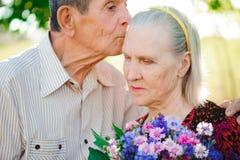 两位老人放松和互相拥抱在公园 免版税库存照片