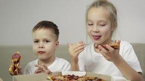 两可爱,吃比萨的滑稽的孩子 男孩微笑,女孩笑并且显示她的手指象 概念:可口 股票录像