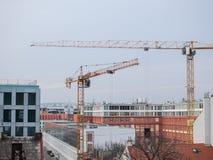 两台建筑用起重机在现代大厦包围的城市 库存照片
