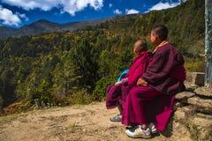 两名年轻佛教新手修士在山坐并且看峰顶,Phajoding修道院,不丹 免版税图库摄影