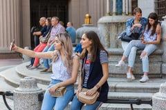 两少女在智能手机坐长凳并且做selfies 免版税库存照片