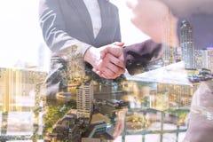 两次曝光商人震动手和交涉和夜城市,成功的讨论概念 免版税库存图片