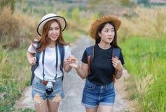 两有背包的女性游人在乡下 免版税库存图片