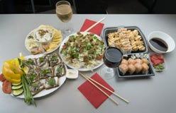 两的一顿美妙的浪漫晚餐与日本卷和杯红酒和白酒 免版税图库摄影
