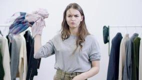 严肃的对照相机的年轻女人投掷的衣裳在衣物屋子 影视素材
