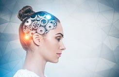 严肃的年轻女人,嵌齿轮脑子 免版税库存图片