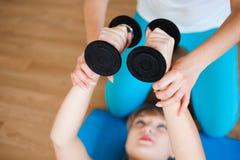 个人要做与哑铃的锻炼的教练帮助的妇女在健身房 免版税库存图片