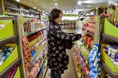 中国妇女高兴发现她喜爱的饼干 深圳 免版税库存照片