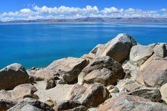 中国 西藏的大湖 湖泰瑞塔西纳木错的商店的大石头在6月 免版税库存图片