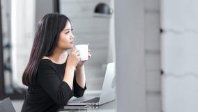 中景相当享用断裂饮用的咖啡的亚裔年轻自由职业者女孩在咖啡馆 影视素材