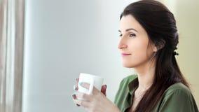 中等作从白色大杯子的特写镜头沉思微笑的妇女饮用的热的饮料 影视素材
