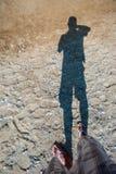 为他的在海滩的阴影照相 免版税库存照片