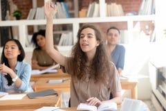 举手的青少年的女性学院大学生在类期间 免版税库存照片