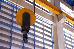举的起重机的起重机勾子在工厂 免版税图库摄影