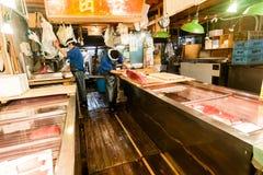 东京,日本- 2010年1月15日:清早在Tsukiji鱼市上 工作者新鲜的金枪鱼为销售做准备 免版税库存照片