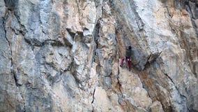 上升在峭壁的人登山人在冬天 上升的结岩石系住二 人攀登在的攀岩运动员富挑战性路线 股票视频