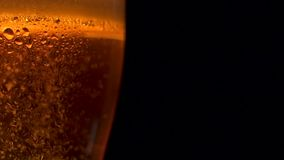 上升冷却的啤酒许多空气金黄泡影的特写镜头在大玻璃的与水下落 股票视频