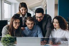 业务会议,做与计算机的年轻工友队巨大企业讨论在共同工作的办公室 配合人概念 免版税库存照片