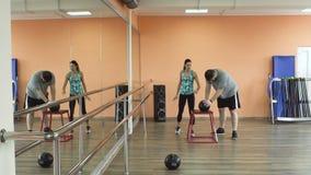 与个人辅导员和做锻炼的肥胖人训练在健身俱乐部 与亭亭玉立一起的厚实的肥胖人 股票录像