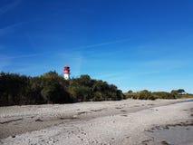 与一座红色白色灯塔的海滩在背景中 库存照片