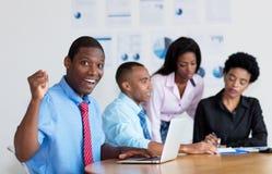 与企业队的欢呼的非裔美国人的商人在办公室 库存照片