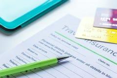 与保险的预定的旅行概念在桌背景 免版税库存图片