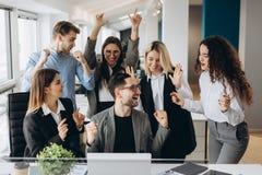 与多种族同事的男性工作者份额喜讯在共有的工作场所,不同的雇员尖叫充满幸福激发与 图库摄影