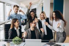 与多种族同事的男性工作者份额喜讯在共有的工作场所,不同的雇员尖叫充满幸福激发与 免版税库存照片