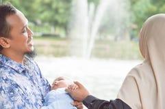与婴孩的年轻回教家庭在湖附近的室外公园有在白天的喷泉的 库存图片