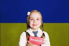 与孩子女孩女学生的乌克兰概念有在乌克兰旗子背景的红色书的 学会乌克兰语语言 免版税库存照片