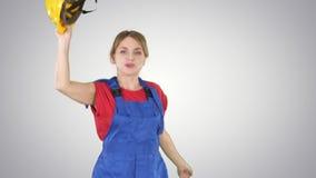 与安全帽的女性建筑工人跳舞在梯度背景 股票视频
