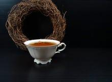 与圆的柳条花圈装饰的热茶杯白色porselain在黑木背景/减速火箭 库存照片