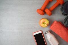与哑铃、蛋白质震动、苹果和毛巾的健身背景 免版税库存照片