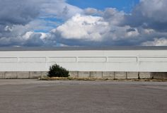 与水泥围墙和一条大柏油路的白色工业仓库大厦在与许多云彩的一天空蔚蓝下 bac 图库摄影