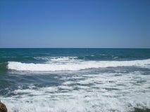 与波浪的一个空的海滩 库存照片