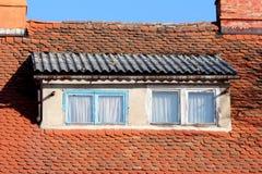与浅兰和白色的屋顶窗口毁坏了木制框架围拢与小瓦和生锈的天沟在两旁边 免版税库存图片