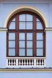 与木制框架的被成拱形的窗口和在底部的装饰白色篱芭在蓝色古老大厦门面  库存图片