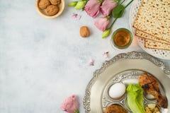 与未发酵的面包、seder板材和春天花的犹太假日逾越节背景 免版税库存照片