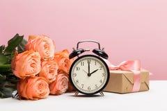 与时钟和礼物的罗斯玫瑰在桃红色背景 免版税图库摄影