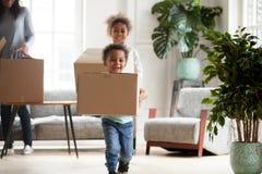 与愉快的箱子的激动的小黑孩子移动  免版税库存照片