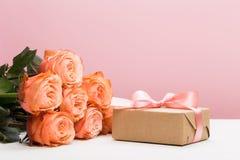 与礼物的罗斯玫瑰在桃红色背景,母亲节,妇女的天 免版税库存图片