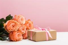 与礼物的罗斯玫瑰在桃红色背景,母亲节,妇女的天 库存图片