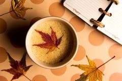 与秋天叶子的咖啡在桌上 免版税库存图片