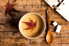 与秋天叶子的咖啡在桌上 库存照片