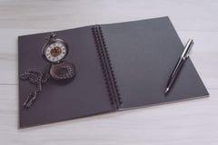 与笔和葡萄酒怀表的空白空的黑页笔记本开头在灰色木桌上使用作为时间,认为的学报, 免版税库存图片