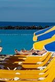 与等待游人,在海滩的有偿的服务的阳伞和椅子的拥挤海滩 图库摄影